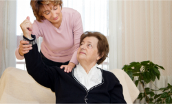 caregiver doing physical therapy with her patient